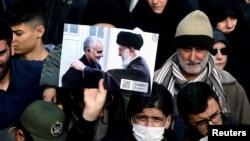 Un manifestant ține o poză a liderului ayatollah Ali Khamenei cu Qassem Soleimani, în timpul protestului împotriva asasinării ultimului, Teheran, 3 ianuarie 2020