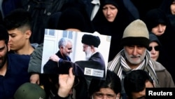A man holding a picture of Qassem Soleimani and Supreme Leader Ali Khamenei during the march against the Qods Force commander's killing.