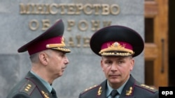 Newly appointed Defense Minister Valeriy Heletey (right) and former acting Defense Minister Mykhaylo Koval (left) talk in front of Defense Ministry headquarters in Kyiv July 3.