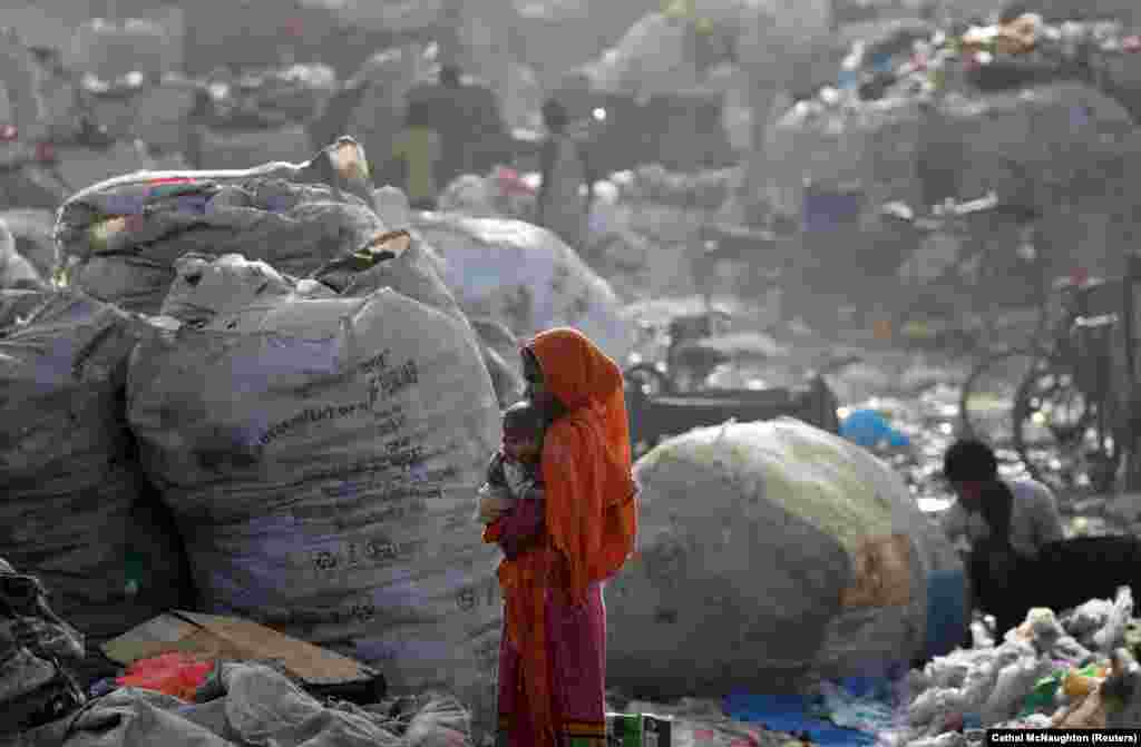 A woman carries her baby through a rubbish dump in Delhi. (Reuters/Cathal McNaughton)