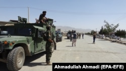 Afghan security officials secure the roads leading to the scene of suicide bomb blasts that killed dozens in the provincial capital of Gardez in Paktia Province on August 3.