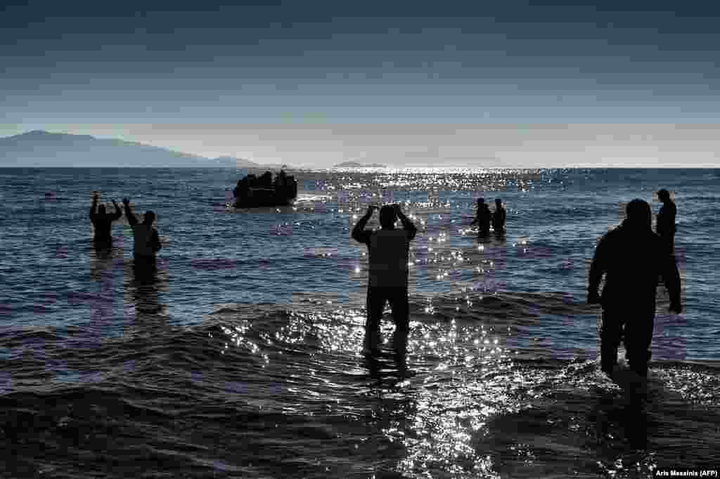 """Активисты неправительственной гуманитарной организации """"Международный центр чрезвычайной помощи"""" (ERCI) показывают на лодку с мигрантами, которая подходит к берегу греческого острова Лесбос, пройдя через Эгейское море из Турции. 22 февраля. (AFP/Aris Messinis)"""