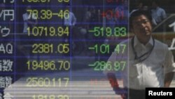 Мужчина смотрит на отражение табло биржи ценных бумаг. Иллюстративное фото.