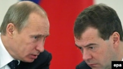 President Dmitry Medvedev (R) speaks with Prime Minister Vladimir Putin during a meeting on the development of the political system in Moscow