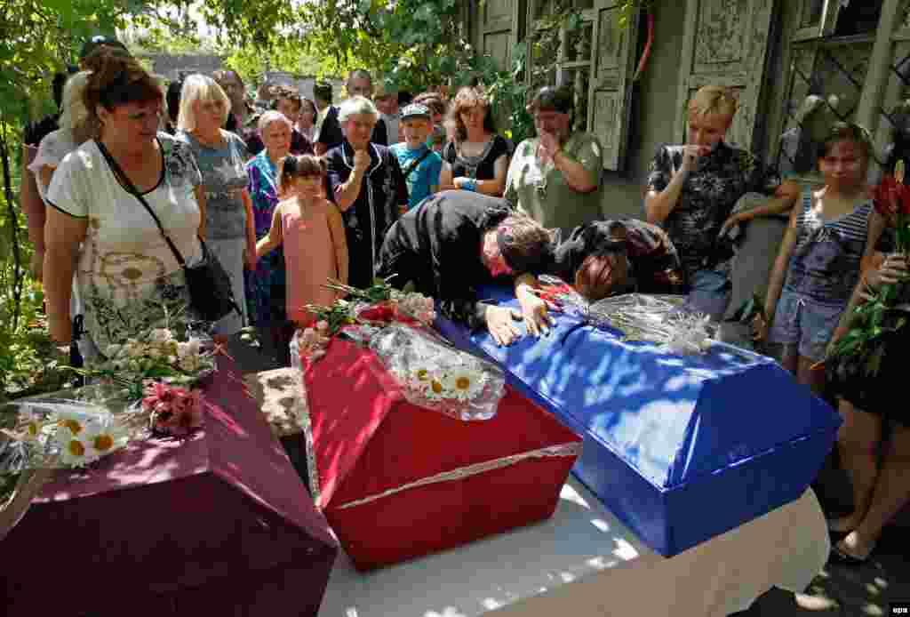 Родичі плачуть на трунах загиблих дітей під час церемонії похорону в Єнакієвому Донецької області у липні 2016 року. Як тоді повідомила Спеціальна моніторингова місія ОБСЄ в Україні, діти знайшли гранату і принесли її додому. Удома граната вибухнула – осколками вона поранила батька і вбила трьох його дітей – 11, 5 і 1,5-річного віку.