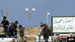 Лібія: паўстанцы праяжджаюць паўз шыльду з прывітальным надпісам для наведвальнікаў гораду Брэга