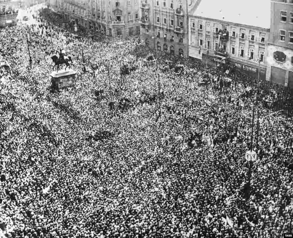 Тысячи людей собираются, чтобы отпраздновать победу над нацистской Германией в Загребе, Югославия, в 1945 году. 29 ноября того же года изгнанный югославский король Петр II был свергнут, а коммунистическое правительство объявило о создании Союзной Народной Республики Югославии.