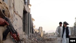 A private security guard at the scene of car bombing in Kandahar. Are the government's forces ready to step in?
