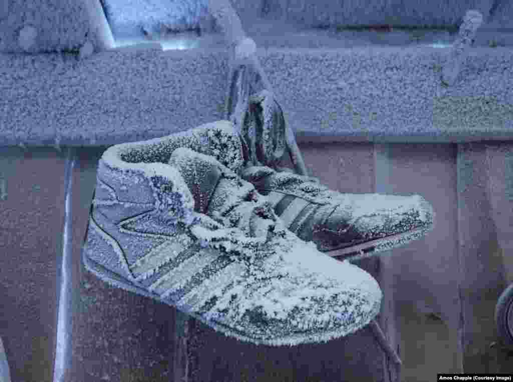 "Frozen shoes in a house in Oymyakon. Chapple says the village guesthouse he stayed in was relatively comfortable, if you used a little creativity: ""The heating pipes near my bed were sizzling hot, but the walls were icy cold. If you wriggled into just the right position between the two, you could get a relatively good night's sleep."""