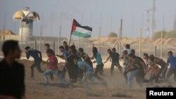 Palestinaly protestçiler Ysraýylyň atan oklaryndan we göz ýaşardyjy gazyndan gaçýarlar.