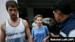 Anastasia Vashukevich (center) and Aleksandr Kirillov (left) arrive at the immigration detention center in Bangkok, Thailand, on February 28.