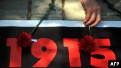 Turkey -- A person lays a carnation on a printed sign during a demonstration marking the 98th anniversary of the massacre and deportation of Ottoman Armenians during World War I, Istanbul, 24Apr2013