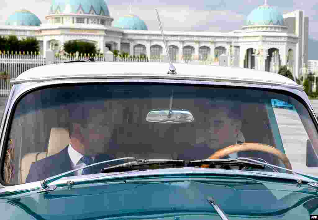 Turkmen President Gurbanguly Berdymukhammedov (right) and Russian Prime Minister Dmitry Medvedev ride in a GAZ-21 Volga car during a meeting in Ashgabat on May 31. (AFP)