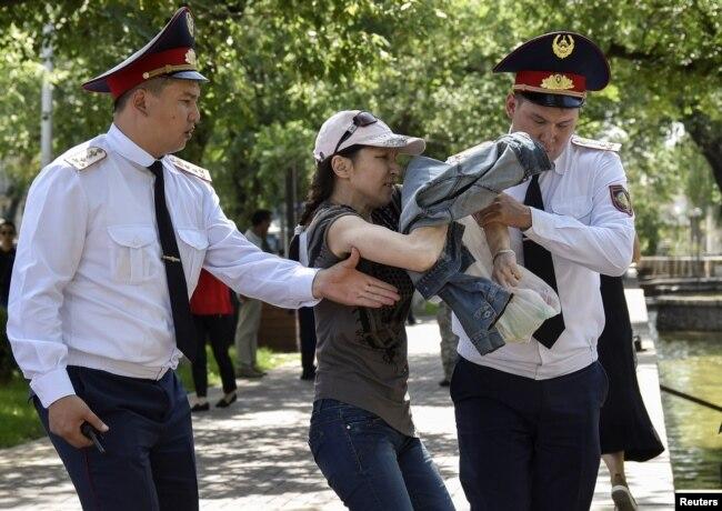 Полицейские задерживают сторонницу оппозиции во время попытки провести митинг, Алматы, Казахстан, 23 июня 2018 года.