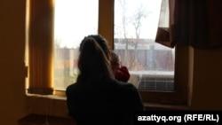 Девочка-подросток со своим ребенком смотрит в окно. Шымкент.