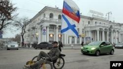 Проруски активист со руско знаме вози велосипед во Севастопол, град во Украина