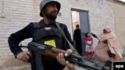 Pakistani security officers escort heath workers as they administer polio vaccinations to children in Peshawar last month.