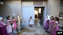 Syrian schoolgirls stand at the entrance of the Saif al-Dawla school as they take part in activities surrounding an art competition organized as part of a local initiative to shift the children's minds from the atrocities of the Syrian war, in the besieged rebel bastion of Douma. (AFP/Abd Doumany)