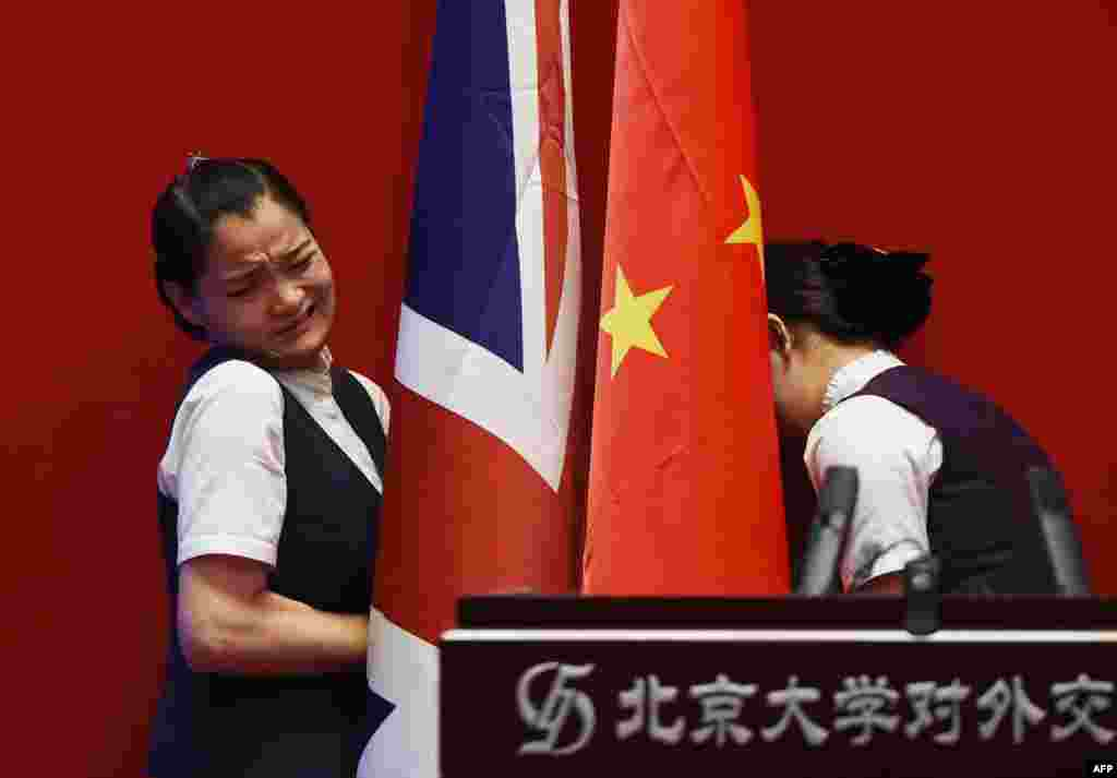 Two attendants install British and Chinese flags behind the podium before a speech by Britain's Foreign Secretary Philip Hammond to students at Peking University in Beijing on August 12. (AFP/Greg Baker)