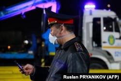 ТЖ кезінде Алматының кіреберісіндегі блокпостта тұрған полицей. 19 наурыз 2020 жыл.