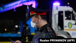 Алматының кіреберісіндегі блокпостта тұрған полицей. 19 наурыз 2020 жыл.