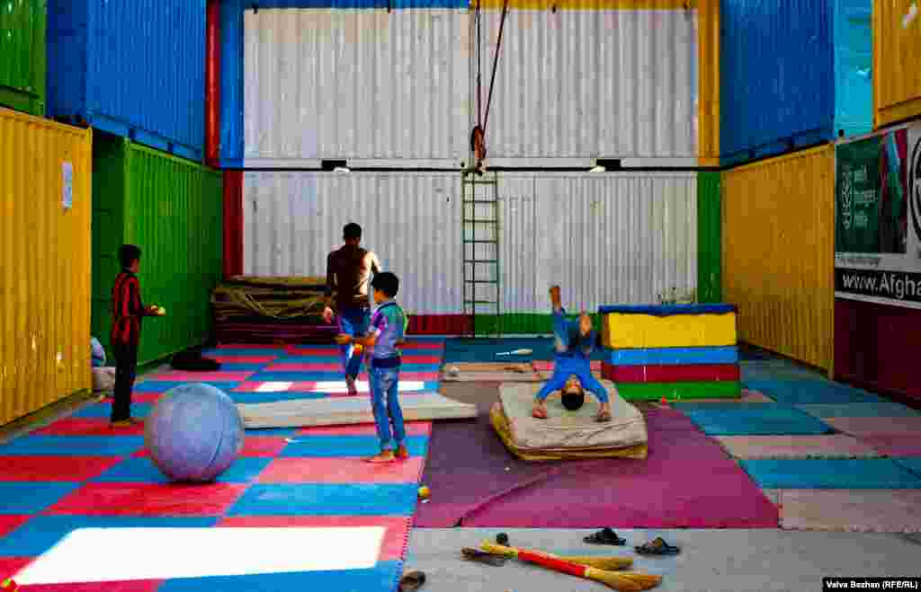 Brightly painted shipping containers have been converted into performance areas where children can practice acrobatics.