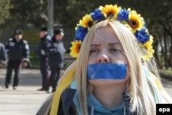 Молодая женщина с заклеенным ртом участвует в проукраинской акции протеста в Симферополе. 13 марта 2014 года.