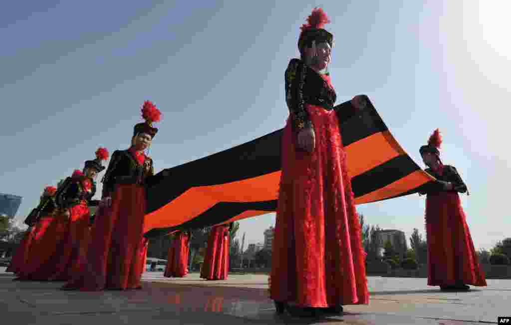 Wearing their traditional costumes, young Kyrgyz women carry a huge St. George's ribbon, a military valor symbol of both Imperial Russia and the Soviet Union, during a ceremony marking the upcoming Victory Day in Bishkek on May 7. (AFP/Vyacheslav Oseledko)