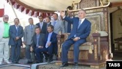 """Нұрсұлтан Назарбаев (оң жақта) президент болып тұрғанда """"Көшпенділер"""" көркем фильмі түсіріліп жатқан алаңда отыр. 17 ақпан 2004 жыл."""