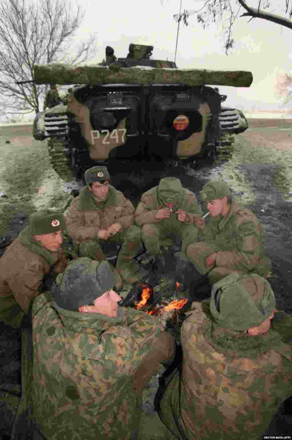 Российские военнослужащие греются у костра в дагестанском Хасав-юрте на границе с Чеченской республикой, ожидая приказа двинуться наГрозный.22 декабря 1994 года.