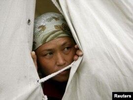 Женщина выглядывает из палатки в лагере беженцев недалеко от Оша. 24 июня 2010 года.