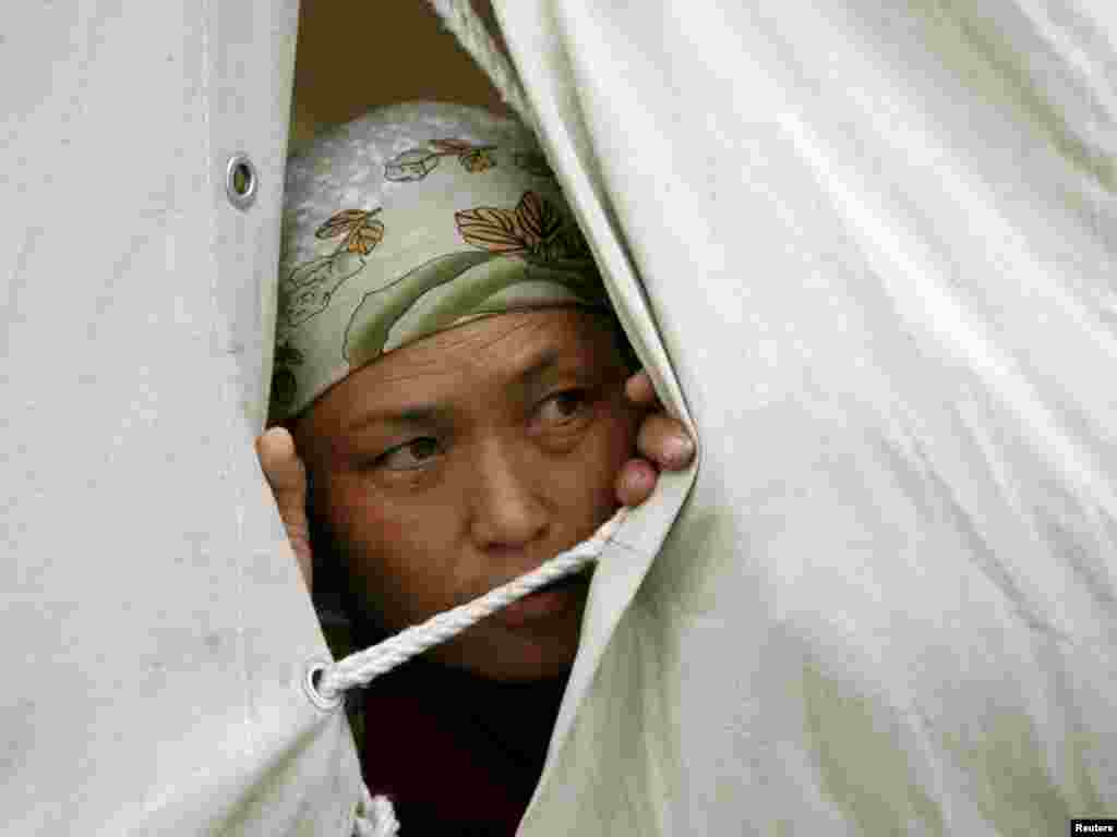 Kyrgyzstan -- An ethnic Kyrgyz woman looks out of a tent at a refugee camp near the city of Osh, 24Jun2010 - An ethnic Kyrgyz woman looks out of a tent at a refugee camp near the city of Osh, June 24, 2010. An international police force may be needed to restore stability in southern Kyrgyzstan after the ethnic bloodshed that has killed hundreds and sparked a wave of refugees, an OSCE official said