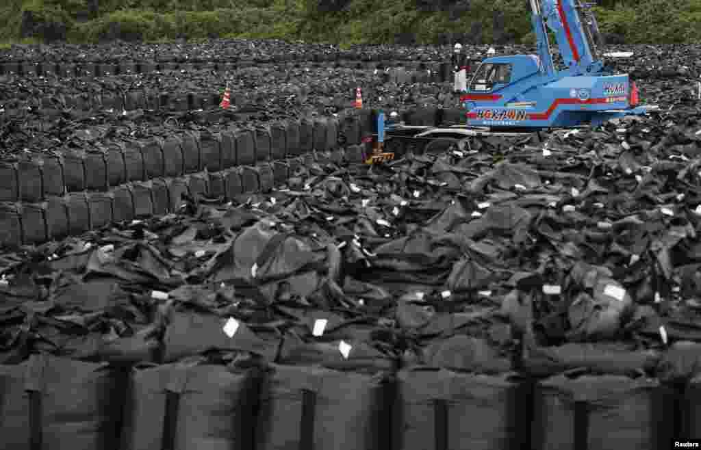 Workers move bags of waste containing soil, leaves, and debris to a storage site in Naraha. The Japanese government is seeking a site for permanent storage of radioactive refuse.