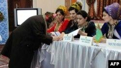Түркіменстандағы президент сайлауында дауыс беруге келген әйел қол қойып жатыр. Ашғабат, 12 ақпан, 2012 жыл.