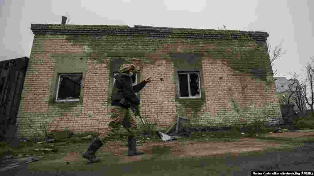 A Ukrainian soldier points toward the zone of combat in an industrial area near Avdiyivka, just north of Donetsk.