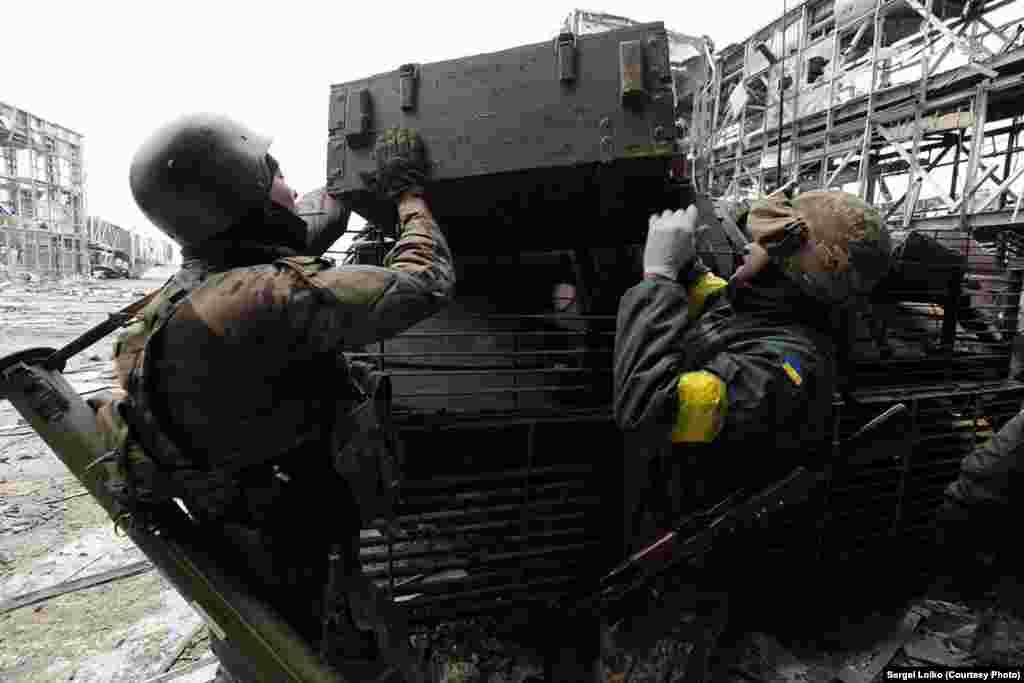 Ящик з останками танкіста вантажать на броньований катафалк. Сепаратисти продовжують обстріл