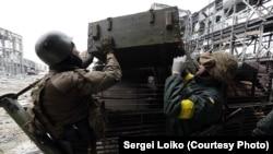 Украинские солдаты загружают тело танкиста, погибшего под обстрелом в районе Донецкого аэропорта. 19 октября 2014 года.