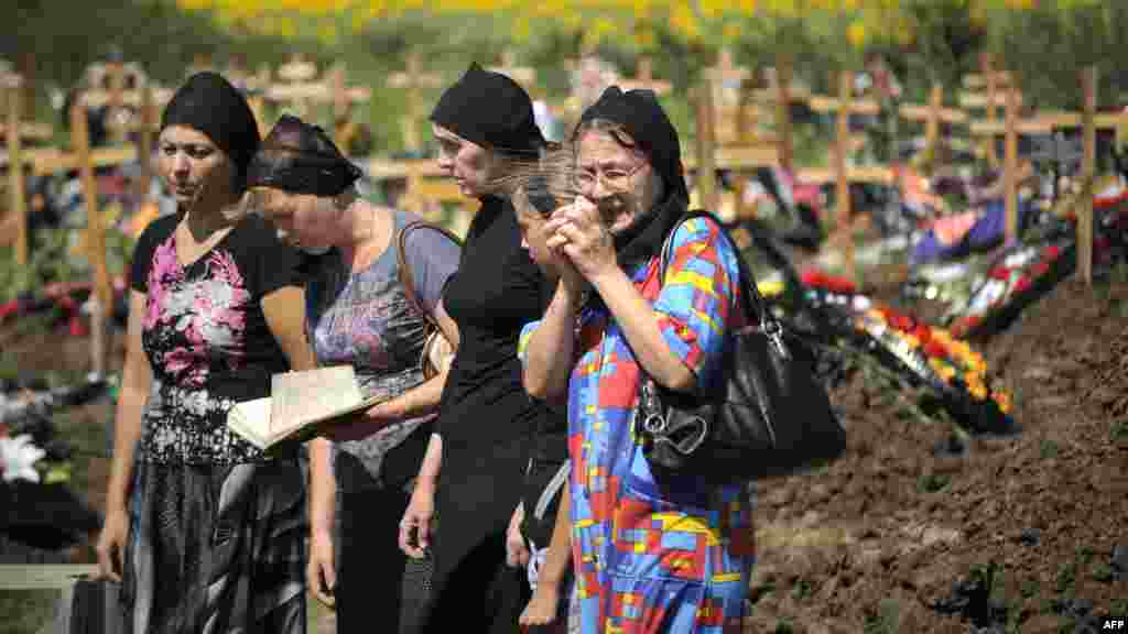 Women mourn at the grave of a flood victim at Krymsk's cemetery on July 9.