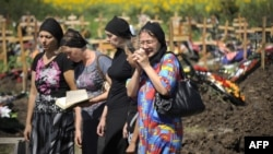 Relatives and friends of a flood victim mourn at his grave in a cemetery in the town of Krymsk in the southern Krasnodar region.