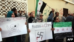 Syrians living in Libya wave the former Syrian flag and hold anti-Russia and -China placards as they protest outside Moscow's embassy in Tripoli on February 5.