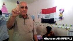 ناخب يلوّح بسبابته البنفسجية بعد اقتراعه في انتخابات مجالس المحافظات، بغداد