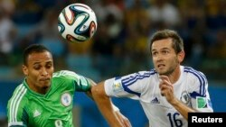 Nigeria's Peter Odemwingie (left) challenges for the ball with Bosnia's Senad Lulic during their 2014 World Cup Group F soccer match at the Pantanal arena in Cuiaba.