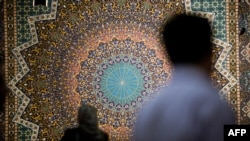 Iran -- People look at a carpet at Iran's international hand-woven carpet exhibition in Tehran, September 29, 2013