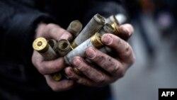 یکی از معترضان پوکههای خالی گلولههای شلیکشده از سوی نیروهای امنیتی را جمع کرده است