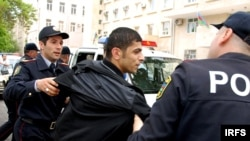 Police detain one of the young protesters in Baku.