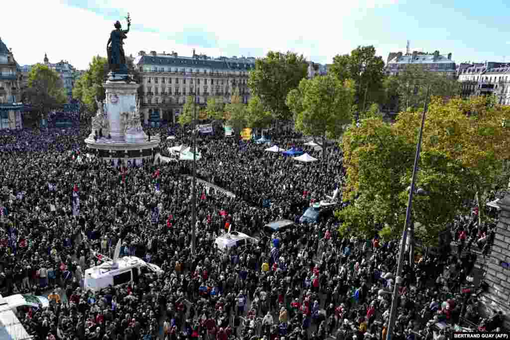 "People gather on Place de la Republique in Paris on October 18, 2020, in homage to history teacher Samuel Paty two days after he was beheaded by an attacker who was shot dead by policemen.  Thousands of people gathered in central Paris on October 18 to pay homage to the schoolteacher decapitated by an ethnic Chechen man for showing cartoons of the Prophet Mohammed to his pupils. The demonstrators laid flowers at the Place de la République in central Paris and held aloft posters declaring: ""No to totalitarianism of thought"" and ""I am a teacher"" in memory of the victim, Samuel Paty."