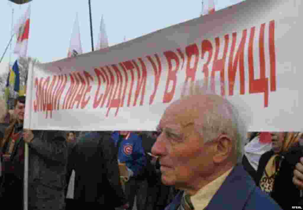 "Banner Day - On Independence Square, an elderly opposition backer stands in front of a banner declaring: ""Miscreant Must Sit In Prison."" (photo: RFE/RL)"