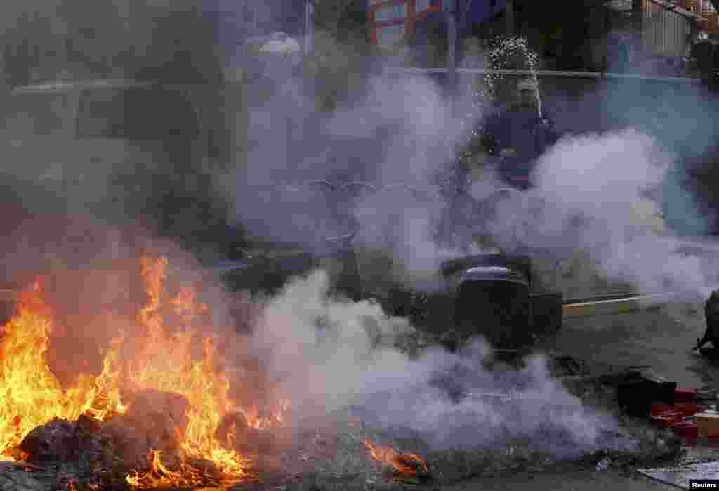 Місцевий житель гасить палаючу барикаду, влаштовану мітингувальниками