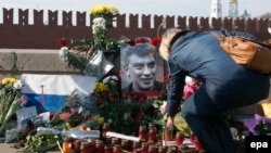 Мәскеуде Борис Немцов қаза болған жерге гүл қойып жатқан әйел.