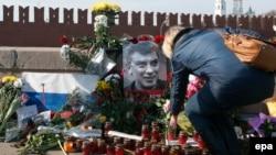 Ресейлік оппозициялық саясаткер Борис Немцов қаза тапқан жерге гүл қойып жатқан әйел. Мәскеу, 9 наурыз 2015 жыл.